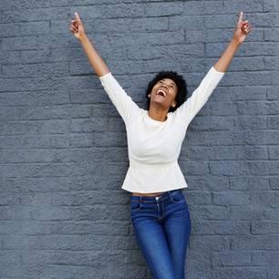 Motivation finden: Junge Frau streckt Arme in die Luft und lacht