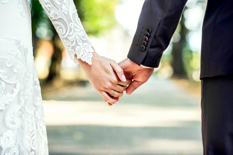 Gute Gründe zu heiraten: Ein Brautpaar hält Händchen