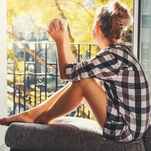 Lichtblicke in der Coronakrise: Eine Frau sitzt am Fenster und schaut raus