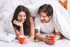 Wie trenne ich Job und Beziehung? Ein glückliches Paar liegt im Bett und lacht zusammen