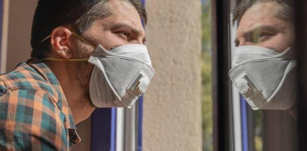 Ein Mann, der mit dem Coronavirus infiziert ist, schaut aus dem Fenster