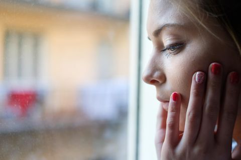 Corona aktuell: Junge Frau am Fenster