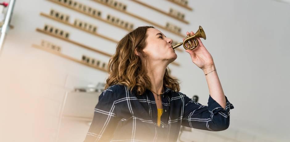 Frau spielt kleine Trompete