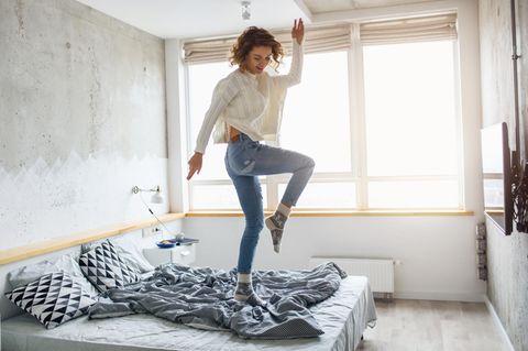 Horoskop: eine fröhliche Frau tanzt auf ihrem Bett