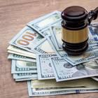 Scheidungskosten: Geldscheine auf Tisch und Gerichtshammer