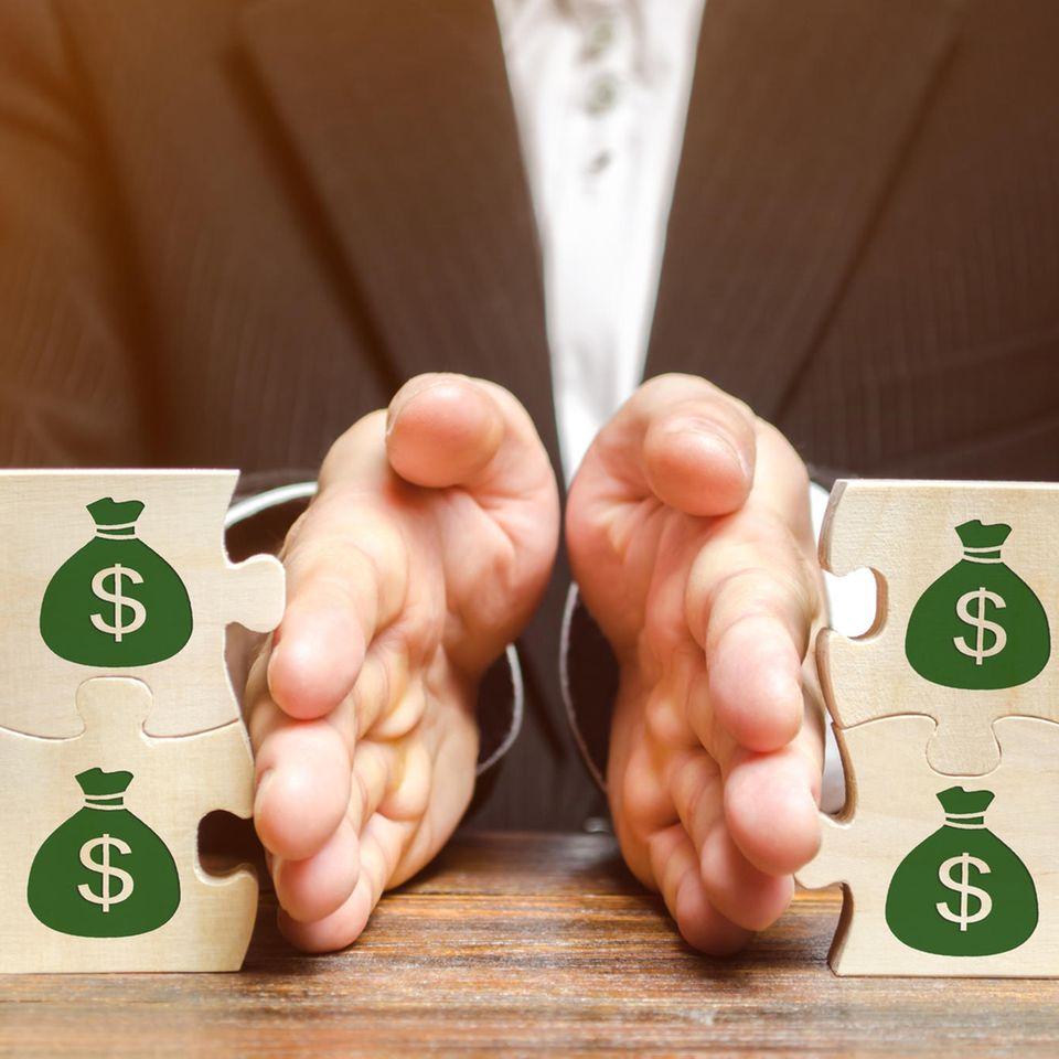 Scheidung und Unterhalt: Puzzleteile mit Dollarzeichen getrennt