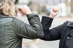 Zwei Frauen begrüßen sich und schützen sich vor Corona