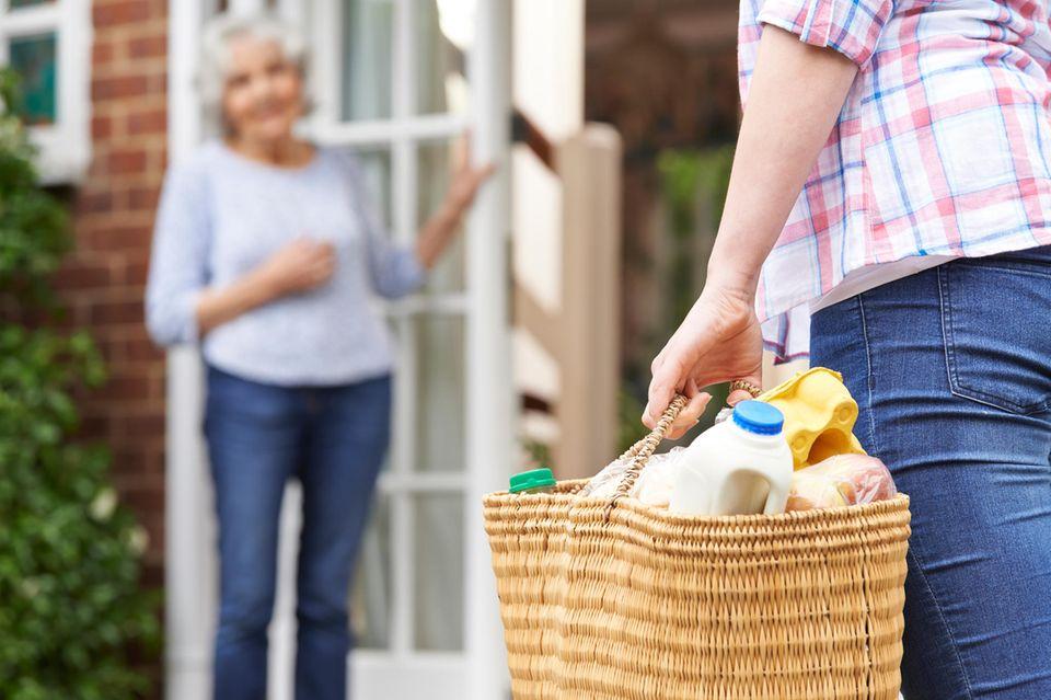 Frau leistet Nachbarschaftshilfe in Zeiten von Corina
