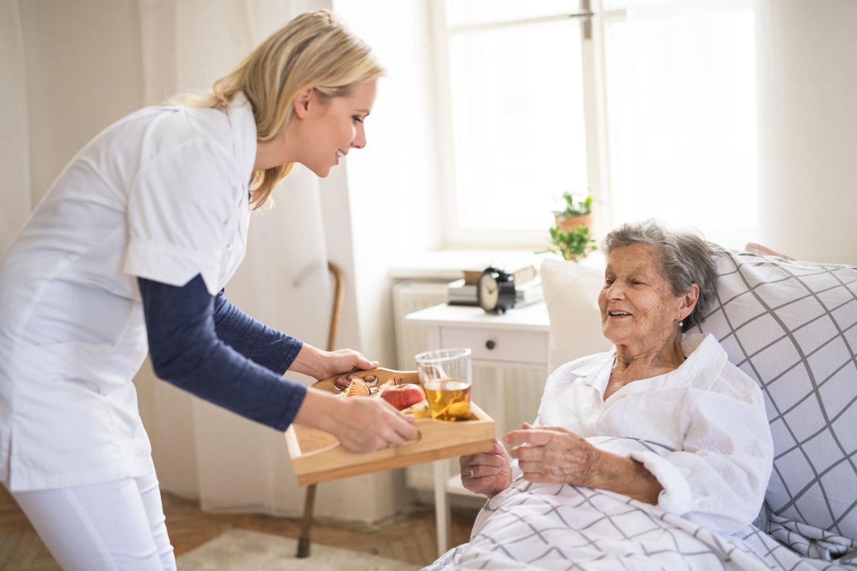 Tagespflege: Pflegerin mit Patientin