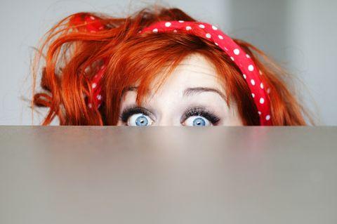 Neugierde: Frau guckt über Wand hinweg