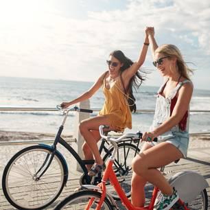 Was ist Freundschaft? Zwei Frauen fahren nebeneinander Rad und halten sich an den Händen