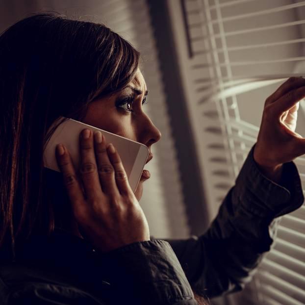 Blaues Wunder erleben: Frau am Handy schaut verschreckt aus Fenster