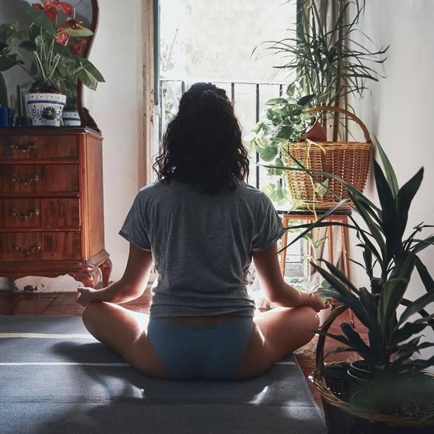 Corona-Tief: Eine junge Frau meditiert im Schneidersitz