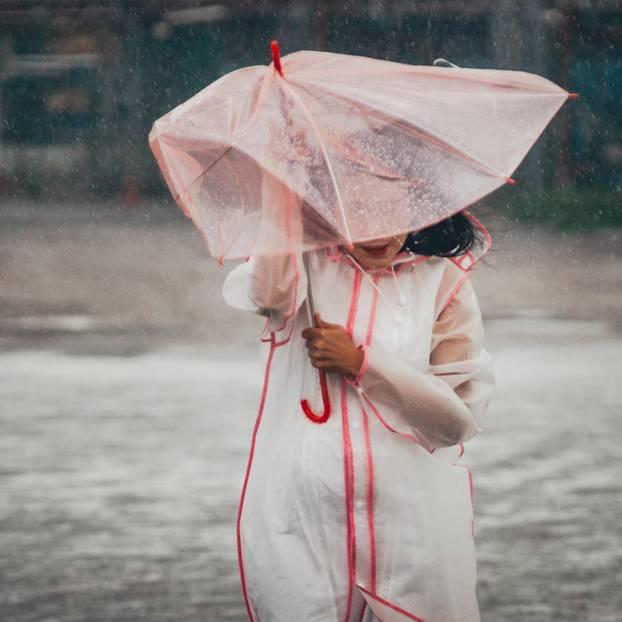 Vom Regen in die Traufe: Frau mit Regenschirm im Regen
