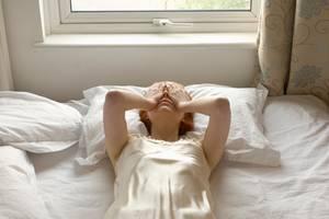 Frau auf Bett mit Händen im  vor dem Gesicht