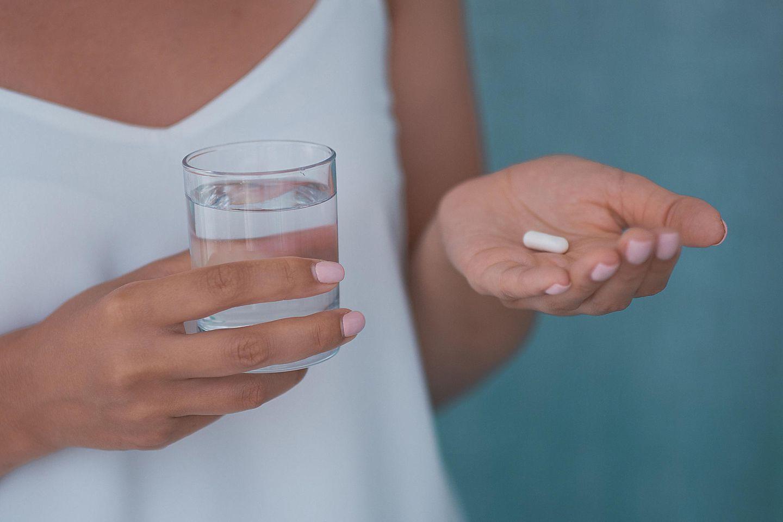 Wann Antibiotika sinnvoll sind: Frau mit einem Glas Wasser und Tablette