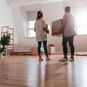 Beim Partner einziehen: Paar steht mit Umzugskartons in Wohnung