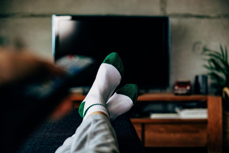 Corona-Panik: Eine Frau sitzt vor dem Fernseher mit den Füßen auf dem Tisch