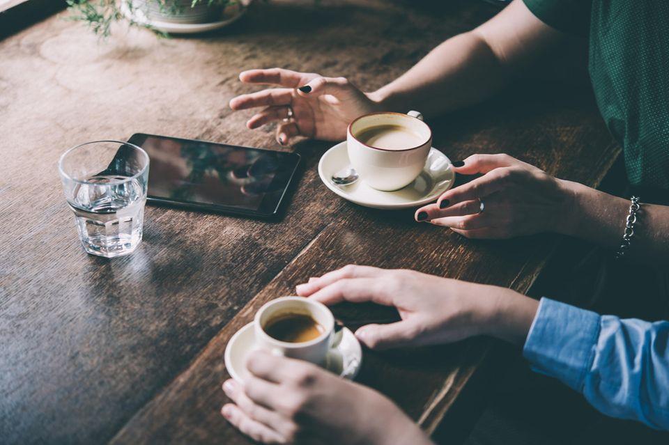 Mit gestressten Menschen reden: Zwei Menschen sitzen am Tisch und trinken Kaffee