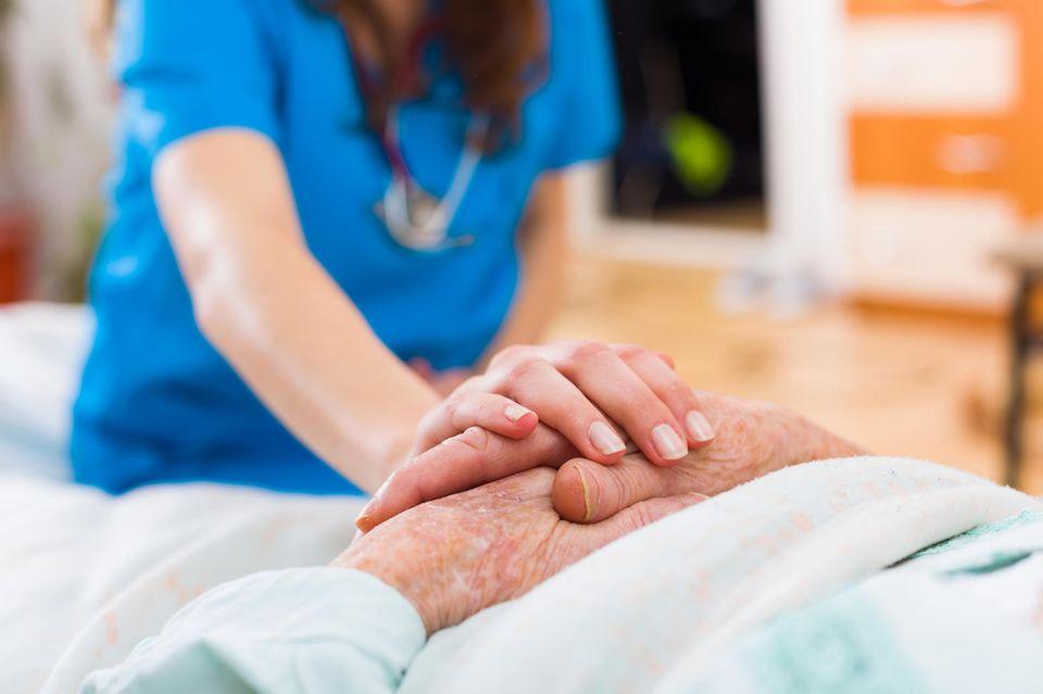 Seniorin im Krankenbett Pflegerin hält ihre Hand