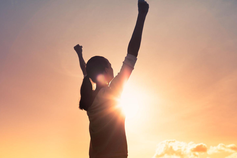Horoskop: Eine Frau bei Sonnenuntergang, die Arme in den Himmel streckend