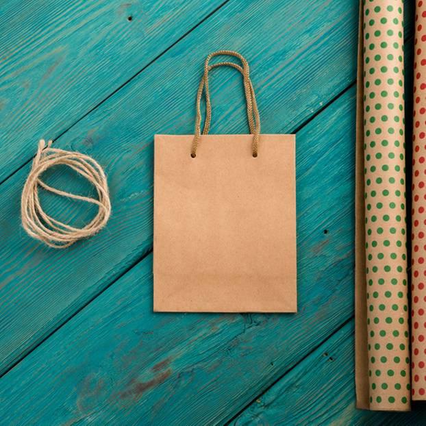 Geschenktüten basteln: Geschenktüte, daneben Geschenkpapierrollen und Sisalband