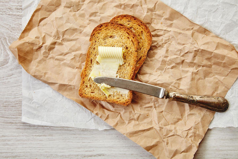 Alles in Butter: Butter auf Brotscheiben geschmiert