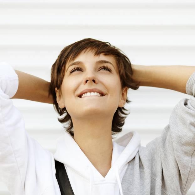 Selbstmotivation: Eine junge Frau guckt motiviert in den Himmel