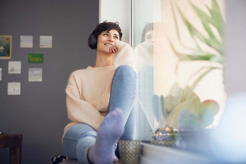 Frau sitzt am Fenster mit Kopfhörern