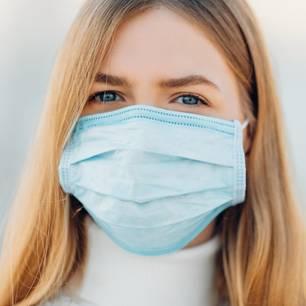 Corona aktuell: Frau mit Mundschutzmaske