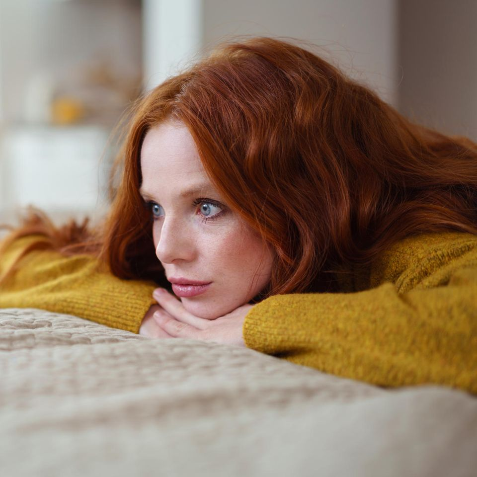 Corona-Fallen, vor denen du dich in Acht nehmen solltest: Eine nachdenkliche junge Frau auf dem Bett