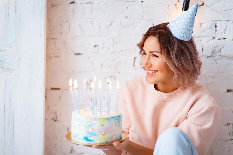 Geburtstag allein feiern: Eine glückliche Frau mit Torte und Hütchen auf dem Kopf
