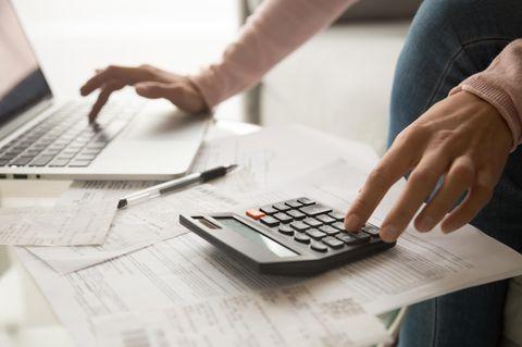 Schufa-Score verbessern: Frau berechnet Schulden mit Taschenrechner