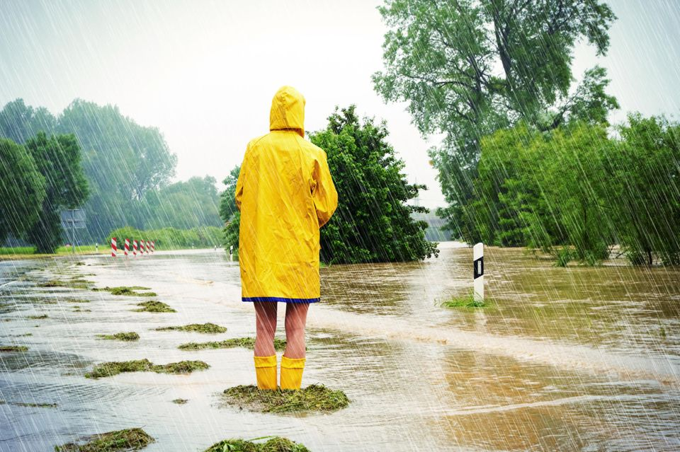 Klimaangst: Person im gelben Regenmantel und gelben Gummistiefeln im Regen