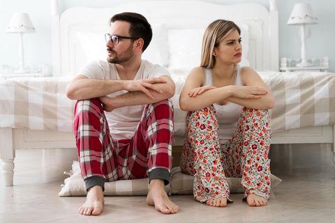 Streit in der Beziehung: Ein Pärchen sitzt schmollend vor dem Bett