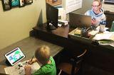 Homeoffice mit Kindern: Frau am Rechner mit Sohn