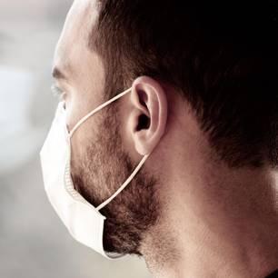 Corona aktuell: Junger Mann mit Atemschutzmaske