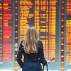 Reise stornieren: Frau vor den Flugplänen am Flughafen