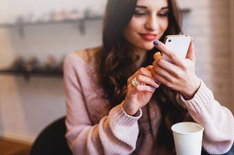 So punktet dein Sternzeichen auf Dating-Apps: Frau am Handy