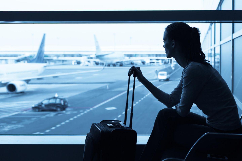 CO2-Ausgleich: Frau mit Koffer am Flughafen