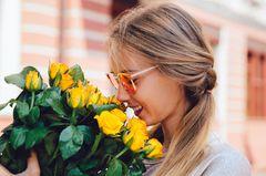 Horoskop: Eine Frau riecht an einem Strauß gelber Rosen