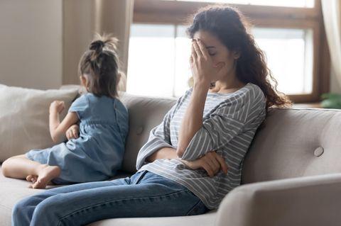 Kündigung nach Elternzeit: Frau mit Hand vorm Gesicht neben Kind