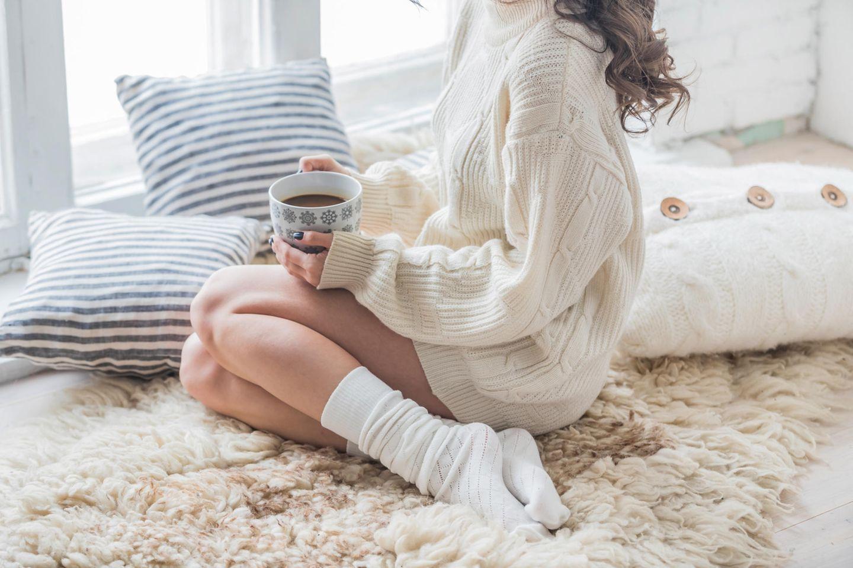Corona-Isolation: Eine Frau sitzt allein zu Hause am Fenster und trinkt Kaffee