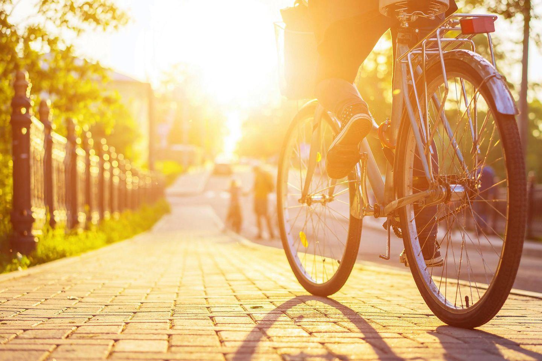Corona-Regeln, die wir nach der Krise beibehalten sollten: Eine Radfahrerin fährt bei Sonnenuntergang eine Straße entlang
