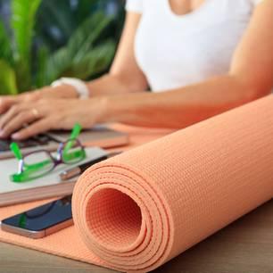 Yoga fürs Büro: Frau am PC mit Yogamatte