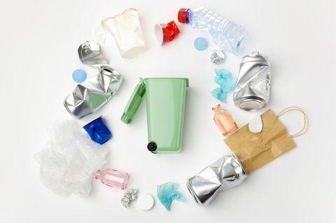 Abfall richtig entsorgen: Mülltonne umgeben von Abfallprodukten