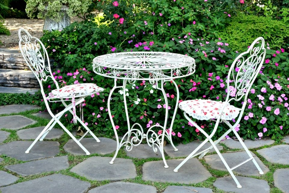 Terrassengestaltung: Gusseiserne Stühle und Tisch im Garten