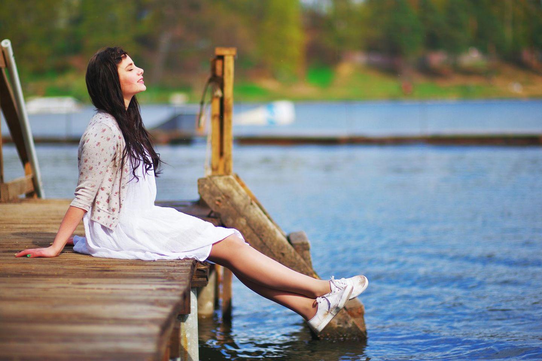 Alleine glücklich sein: Eine Frau sitzt am See und genießt die Sonne