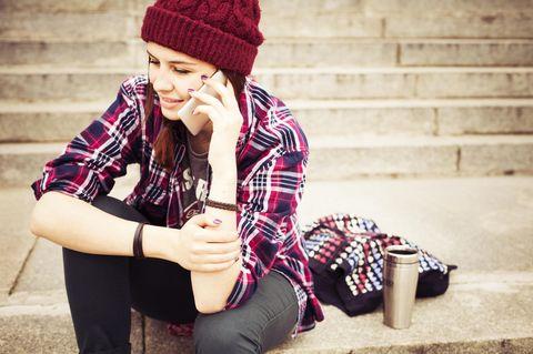 Leid vergleichen: Eine junge glückliche Frau telefoniert