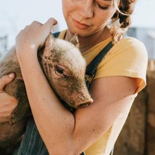 Umwelt schützen: Frau mit Schwein auf dem Arm